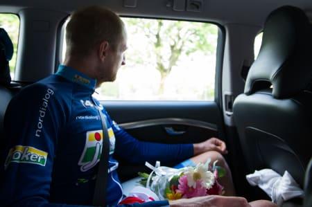 PÅ VEI HJEM: Reidar Borgersen tenker gjennom dagen, etter premieseremonien. I fanget har han blomster, en plakett og den røde trøyen han brukte på podiet.
