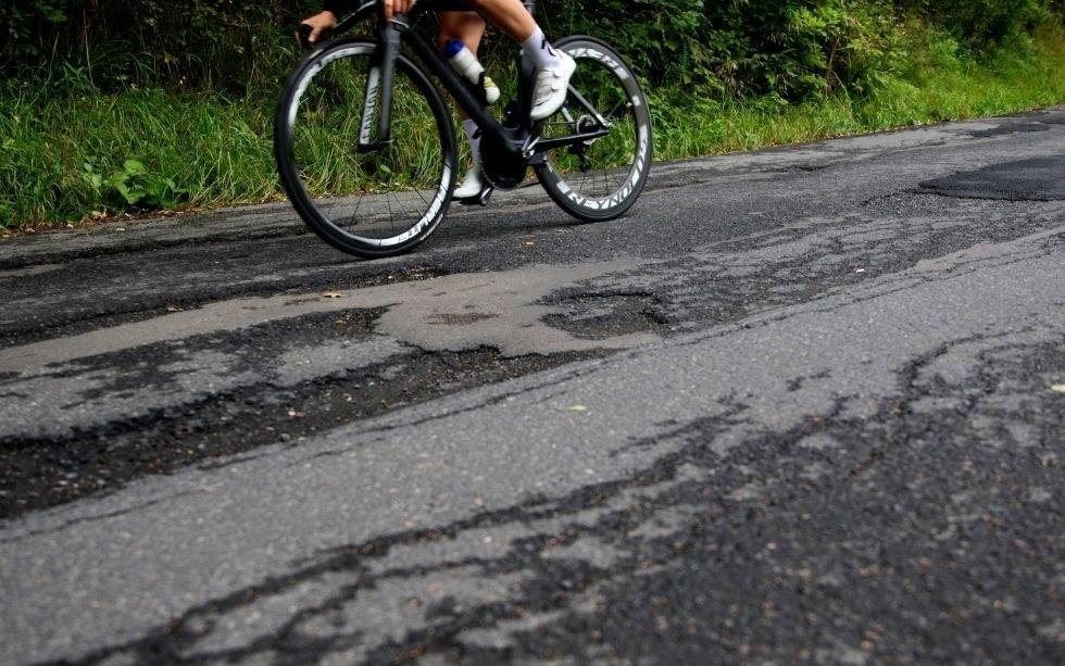 Syklist med karbonhjul og hull i asfalten