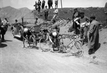 VOULEZ-VOUS Di2? Philippe Thys og Théophile Beeckman bytter utveksling et sted mellom Nice og Briancon. Man hadde to tannhjul på hver side av bakhjulet, men bakgir drev man ikke med i Tour de France. Slikt var for pingler, mente Henri Desgrange, og da ble det slik helt til 1937. Foto: Presse Sports