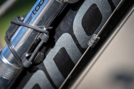 BESKYTTELSE: Utenpåliggende vaiere elsker å lage slitasje på ramma. Tre små gummikringler skal beskytte lakken. Holder det?