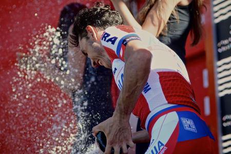 LITEN RÅTASS: Joaquin Purito Rodriguez feirer seieren opp Alto del Naranco med å dynke podiumpikene med cava fra hovedsponsor Grand Ducay.