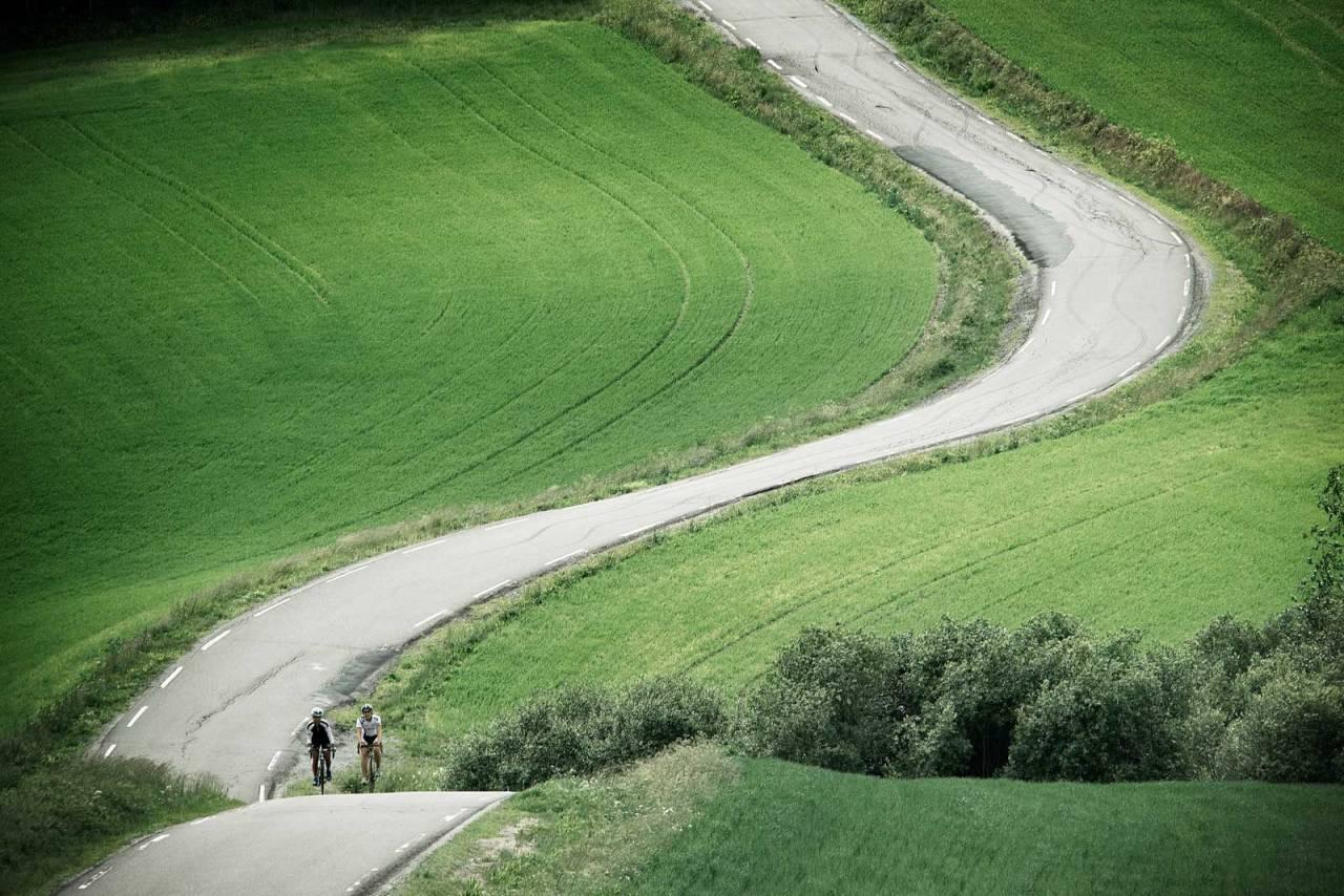 SÅ LANGT ØYE REKKER: Hvitstiplet asfalt, kulete terreng og frodig kulturlandskap er stikkordene for Follorunden. Det blir så mye at Kathrine Hofstad og Line Gulliksen nesten går lei. Foto: Kåre Dehlie Thorstad